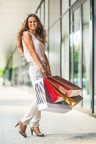smiling young woman with shopping bags at a mall